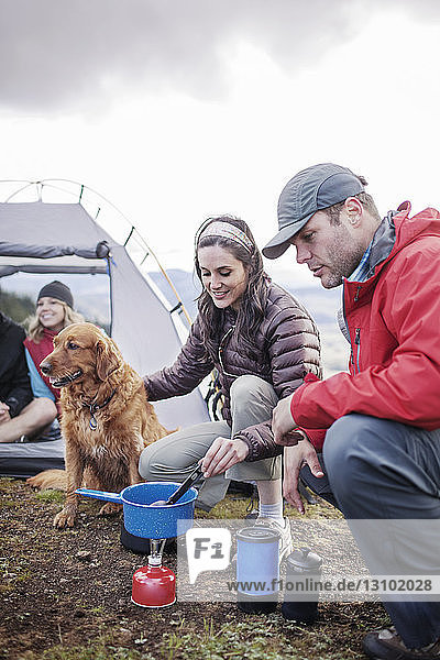 Friends preparing food by dog at campsite