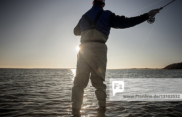 Rear view of man fishing at sea during sunset