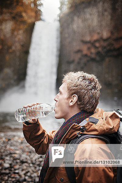 Side view of male hiker drinking water from bottle while standing against waterfall
