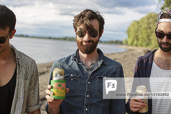 Male friends holding cans while standing at riverbank