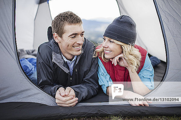Happy couple lying in tent at campsite