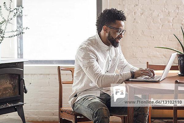 Glücklicher junger Mann benutzt Laptop zu Hause