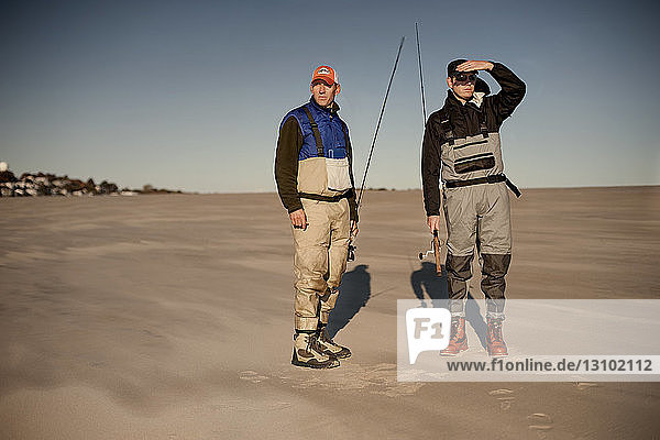 Friends holding fishing rods standing on sand against clear sky