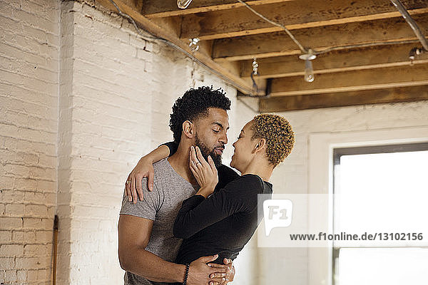 Romantic young couple embracing in bedroom