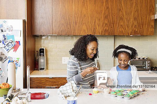 Mutter assistiert Tochter beim Streuseln von Cupcakes