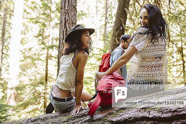 Porträt einer lächelnden Frau mit Freunden beim Geniessen im Wald