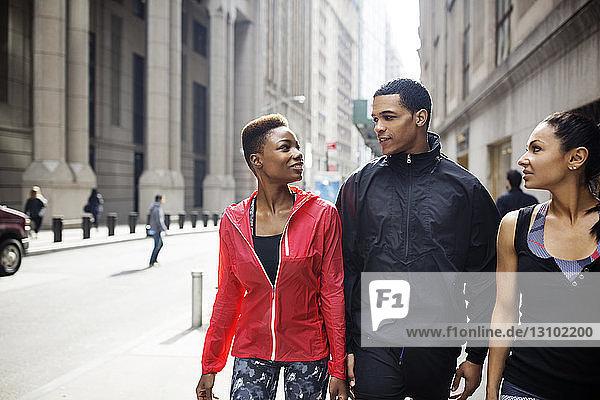 Sportler unterhalten sich beim Gehen auf dem Bürgersteig in der Stadt