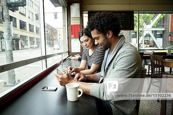 Multi-ethnisches Paar benutzt Tablet-Computer im Café