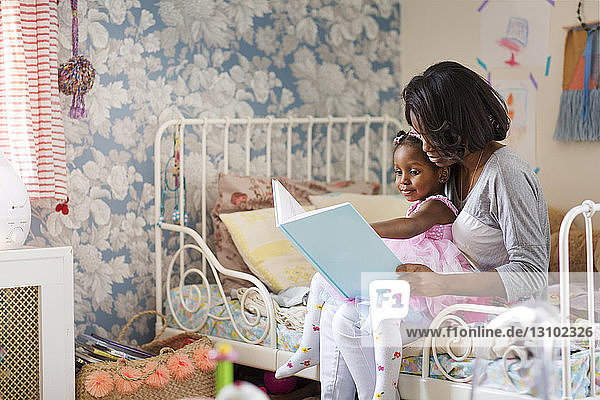 Girl looking at picture book with mother in bedroom
