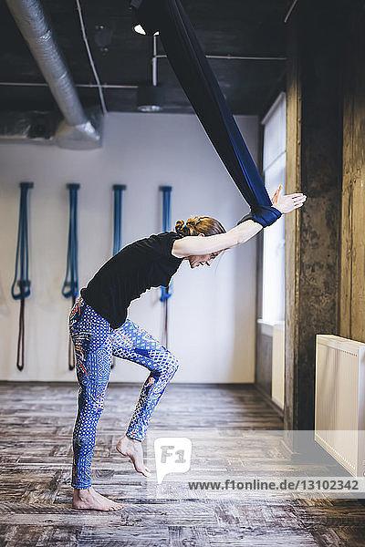 Seitenansicht einer Frau  die eine Hängematte benutzt  während sie im Fitnessstudio trainiert