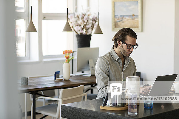 Confident man using laptop computer at home