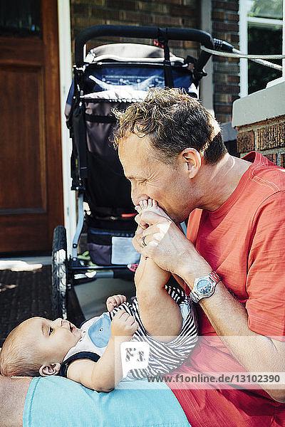 Seitenansicht eines Vaters  der die Füße eines Babys küsst  während er am Eingang sitzt