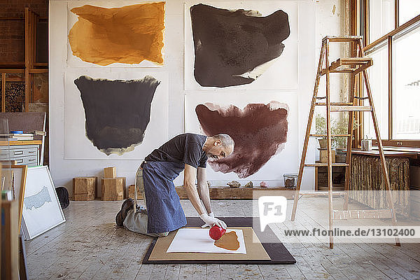 Full length of male artist making painting in workshop