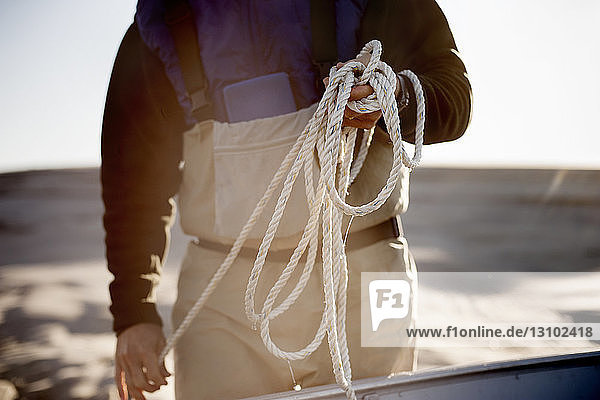 Midsection of man holding rope while standing at beach