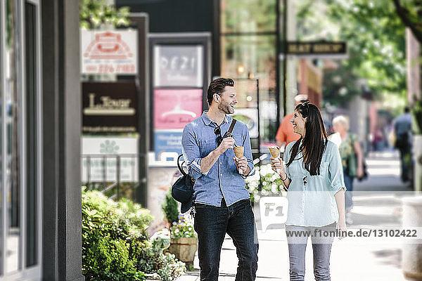 Glückliches Paar isst Eiscreme beim Spaziergang auf dem Bürgersteig in der Stadt
