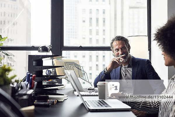 Businessman talking with female colleague while sitting against window in office