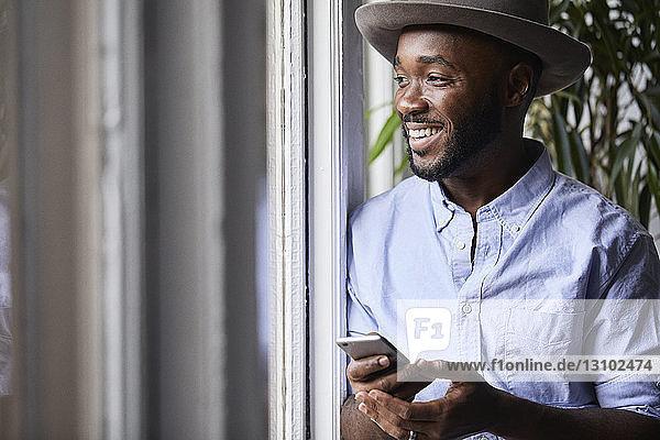 Lächelnder Geschäftsmann  der ein Smartphone benutzt  während er im Kreativbüro am Fenster steht