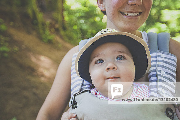 Midsection of smiling mother carrying son in baby carriage