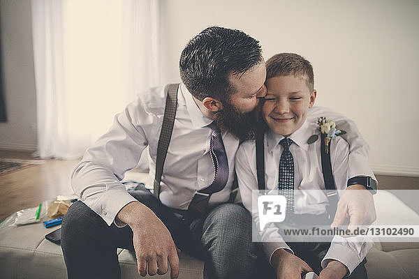 Happy bridegroom kissing pageboy while sitting on bed at home