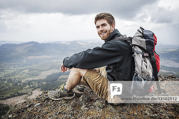 Portrait of smiling man carrying backpack while sitting on mountain