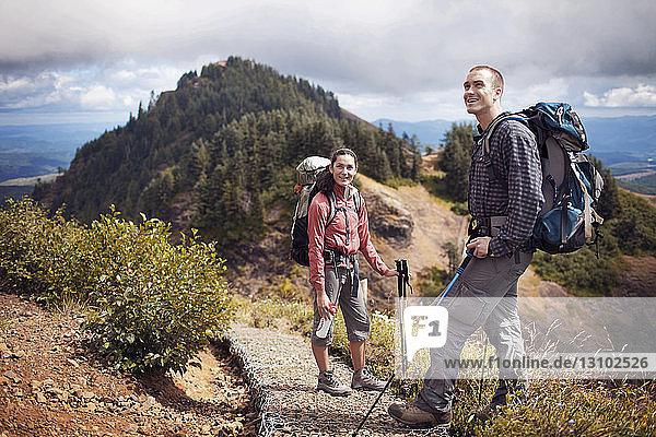 Glückliches Paar wandert auf Berg gegen wolkigen Himmel