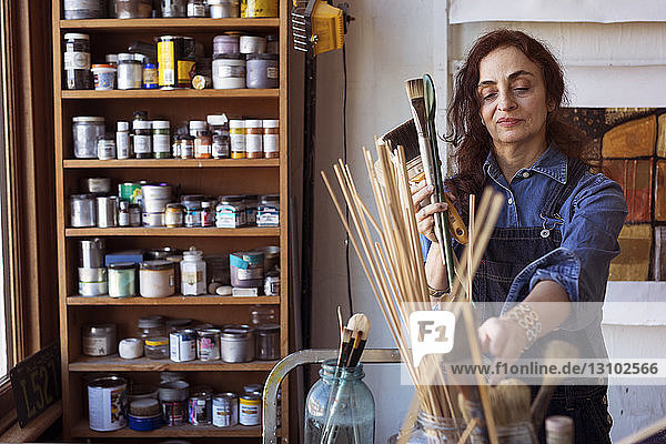 Artist holding paintbrushes in workshop