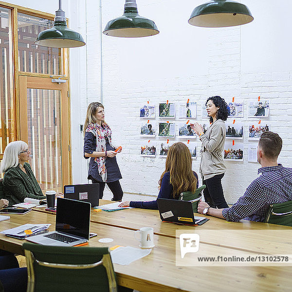 Businesswoman explaining to colleagues in meeting at board room