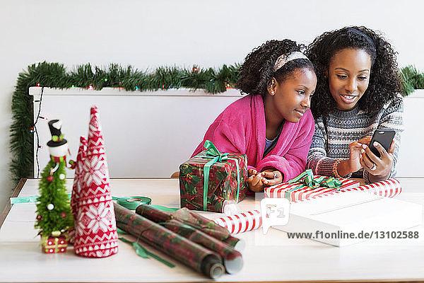 Mutter und Tochter telefonieren mit dem Handy  während sie mit Geschenken am Tisch sitzen