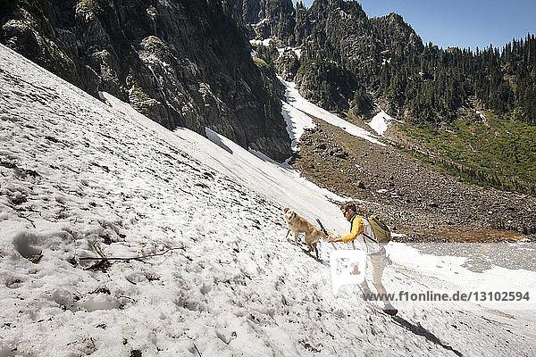 Seitenansicht eines Mannes beim Spaziergang mit Hund auf einem schneebedeckten Berg