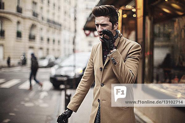 Mann raucht Zigarre  während er auf einem Fußweg steht