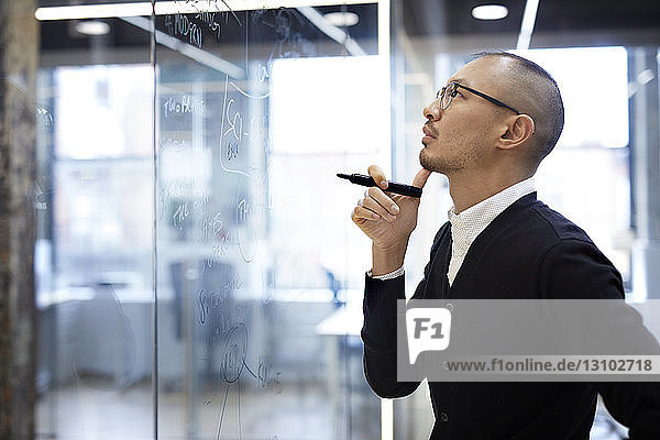 Business man looking at plan on glass wall in office