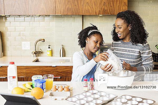 Mutter sieht Tochter an  die Mehl in Schüssel mischt