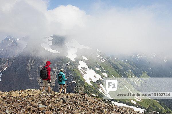 Rückansicht von Wanderern  die auf dem Berg vor bewölktem Himmel stehen