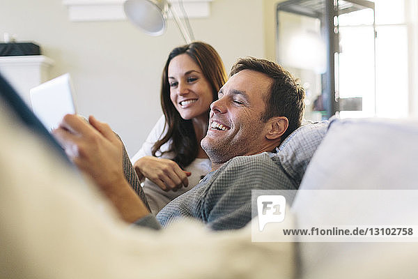 Happy couple using digital tablet while relaxing on sofa at home