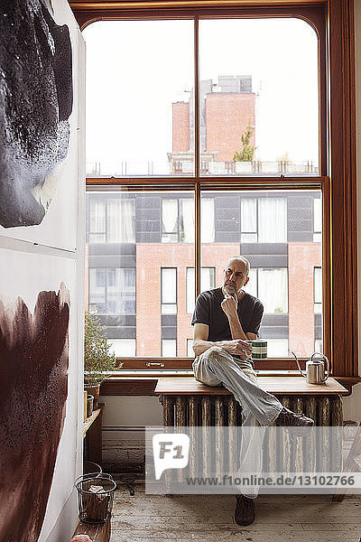 Thoughtful artist holding coffee cup while sitting by window at workshop