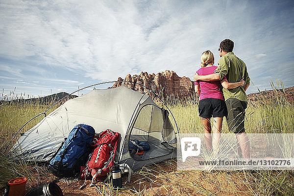 Rückansicht eines Paares  das auf einem Grasfeld vor bewölktem Himmel steht