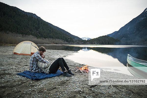 Freund umarmt Freundin  während er auf einer Picknickdecke am Seeufer am Lagerfeuer bei klarem Himmel sitzt