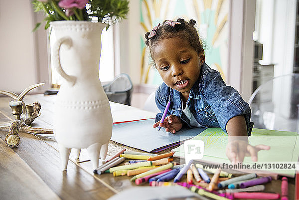 Cute girl reaching for colored crayons on table at home