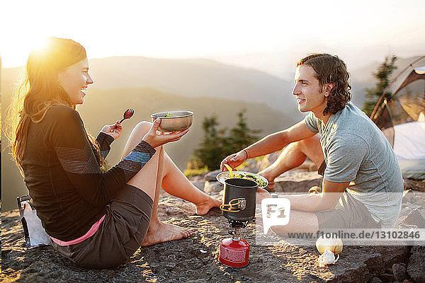 Glückliches Paar isst  während es auf einem Berg vor klarem Himmel sitzt