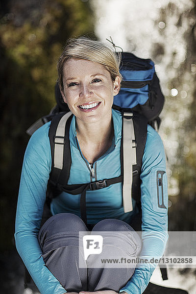 Portrait of happy female hiker carrying backpack