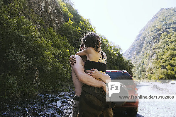Couple embracing while kissing against mountains