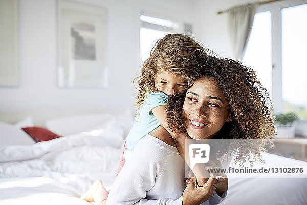 Happy daughter embracing mother sitting on bed at home
