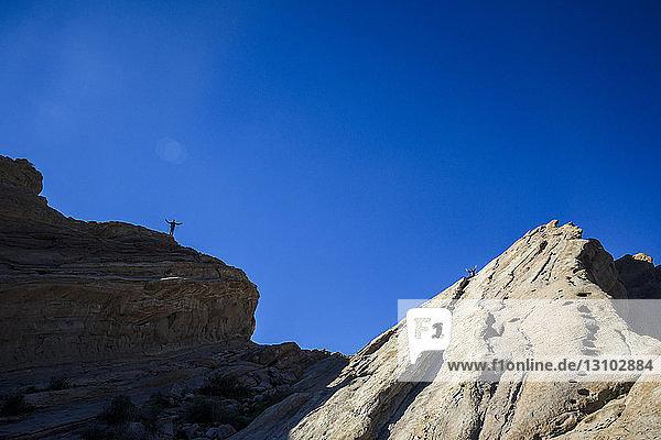 Fernsicht auf Freunde  die auf Felsformationen vor klarem blauen Himmel stehen