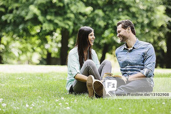 Glückliches Paar sieht sich an  während es sich auf einer Wiese im Park entspannt