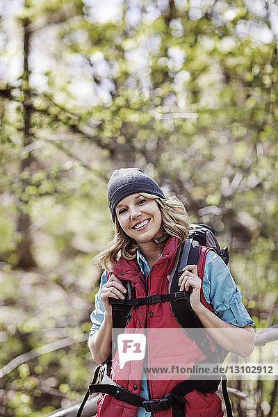 Portrait of happy female hiker standing in forest