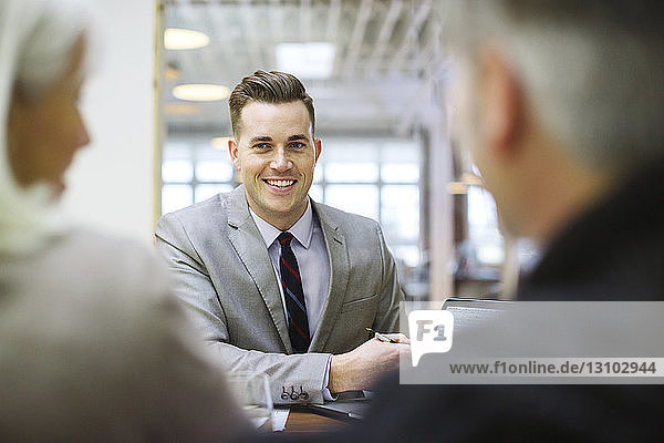 Smiling businessman explaining to colleagues over laptop computer in office