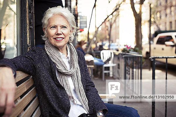 Nachdenkliche ältere Frau sitzt auf Bank am Bürgersteig