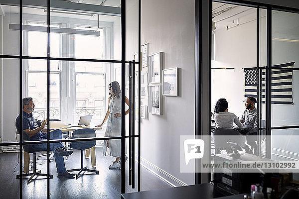 Unternehmer diskutieren in Vorstandsetagen in einem kreativen Büro mit Blick durch Fenster