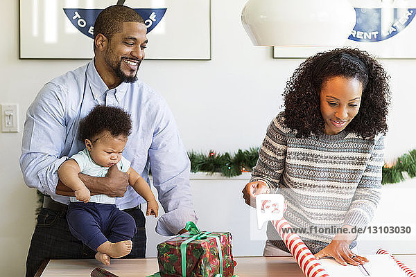 Mann mit Sohn betrachtet Frau beim Einpacken des Geschenks zu Hause