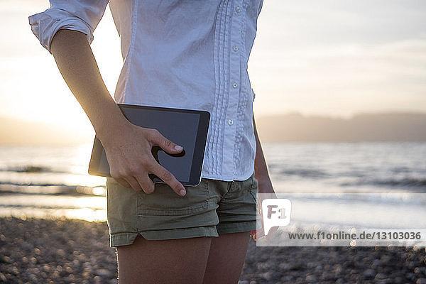 Mittelteil einer Frau  die eine Tablette hält  während sie am Ufer gegen den Himmel steht